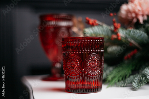 table setting for a festive event or family dinner: decoration with ecological, natural decor-spruce, cotton, rose. Holiday card for Mother's Day or Women's Day. Use of wax candles and clear mugs.