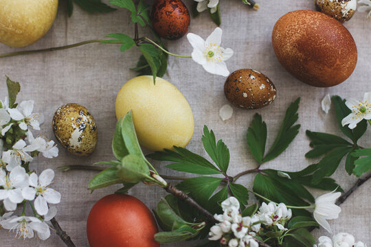 Modern easter eggs with spring flowers flat lay on rustic linen cloth. Happy Easter! Aesthetic