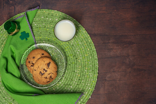 St Patrick's Day treat of cookies and milk on a glass plate with placemat, napkin, shamrock and tiny leprechaun hat on a wood table background