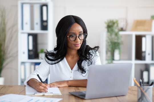 Happy black young business lady working on laptop at office, taking notes during online work meeting or webinar