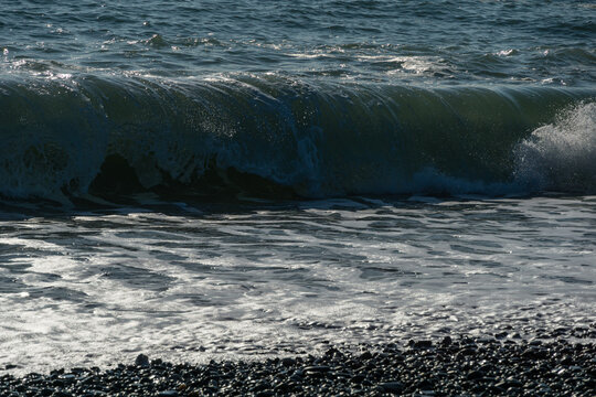 White wave breaking on Sochi Black Sea coast. White spray and foam in the foreground. Emerald blue sea water beyond. December winter sea in southern resort of Russia.