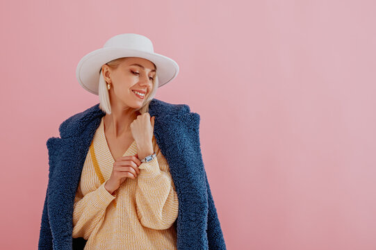 Happy smiling fashionable woman wearing trendy blue faux fur coat, yellow v-neck sweater, white hat, elegant wrist watch, posing on pink background.  Copy, empty space for text