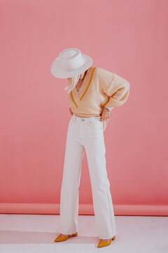 Elegant woman wearing trendy yellow v-neck sweater, white wide leg jeans, hat, pointed toe shoes, posing on pink background. Spring fashion conception. Full-length portrait