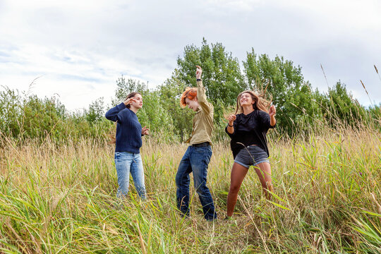 Summer holidays vacation happy people concept. Group of three friends boy and two girls dancing and having fun together outdoors. Picnic with friends on road trip in nature.