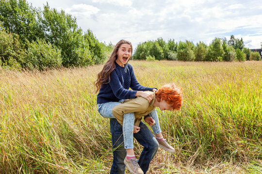 Summer holidays vacation happy people concept. Loving couple having fun in nature outdoors. Happy young man piggybacking his girlfriend. Happy loving couple embracing outdoor at summertime.