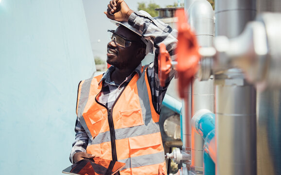 Africa American worker wearing safety goggles check condition of crude oil centrifugal pump and lube oil system. Metal lathe industrial manufacturing factory outside. Hard working concept