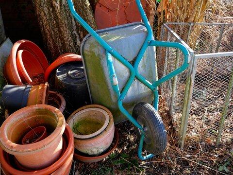 Schubkarren und alte Pflanztöpfe im Garten