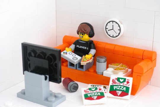 Tambov, Russian Federation - February 24, 2021 Lego video game guy minifigure sitting on a couch playing video games and eating pizza.