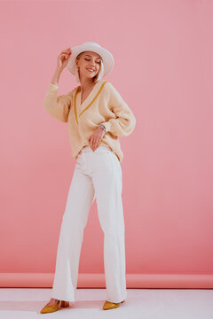 Happy smiling lady wearing trendy yellow v-neck sweater, white wide leg jeans, hat, pointed toe shoes, posing on pink background. Spring fashion conception. Full-length portrait