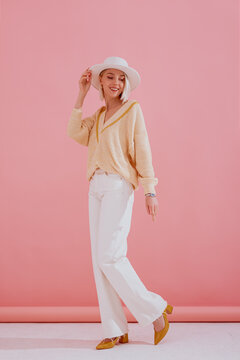 Happy smiling girl wearing trendy yellow v-neck sweater, white wide leg jeans, hat, pointed toe shoes, posing on pink background. Spring fashion conception. Full-length portrait