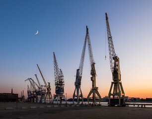 Old harbor crane silhouettes under a crescent moon. Antwerp, Belgium.