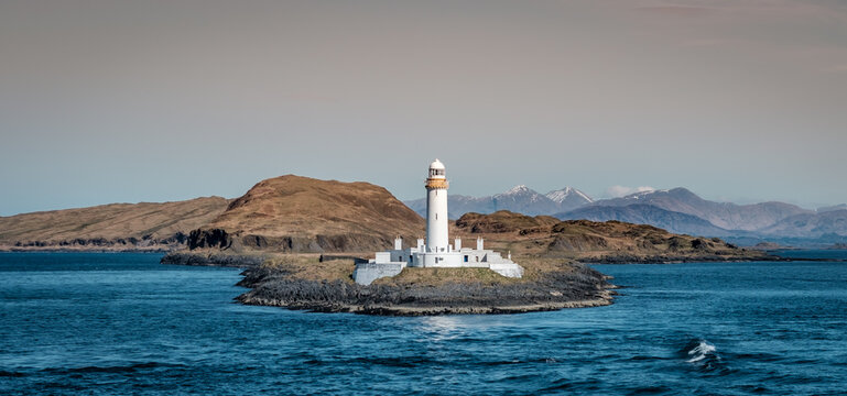 View on the old Eilean Musdile lighthouse in Scotland, with snowcapped highland peaks in the background