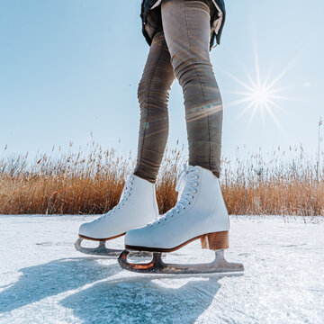 Young woman ice skating outdoors on a pond on a freezing winter day. Detail of skate shoes.