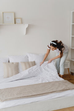 Young beautiful woman making bed.