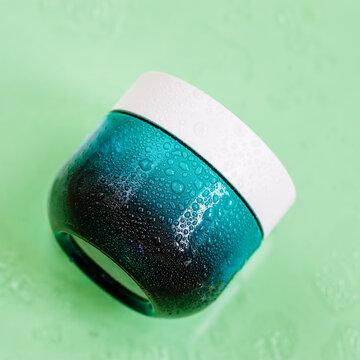 Natural organic cream in blue glass jar, water bubbles, light background. Skincare, moisturizer, minimalism style