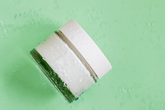 Glass round jar of moisturizing cream, skin care, top view, green background, water drops. Concept of freshness, beauty