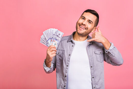 Happy winner! Call me sign. Young rich man in casual holding money dollar bills with surprise isolated over pink background.