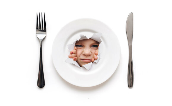 Plate, fork and knife lie on a white tablecloth. Child girl looks through a hole in a plate with wide open eyes. The concept of dislike for certain foods and poor appetite in childhood. Copy space.
