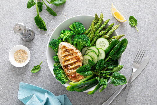 Chicken breast grilled, broccoli with asparagus and fresh green vegetables, spinach leaves in lunch bowl, healthy food, top view