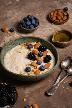 Oatmeal porridge with nuts, fresh berries and honey in a ceramic bowl on rustic background