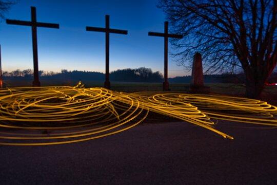 Gelbe Lichtmalerei in einer düsteren, dunklen Umgebung vor drei Kreuzen in Bayern, Deutschland.