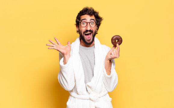 young bearded man wearing bathrobe with a chocolate donut