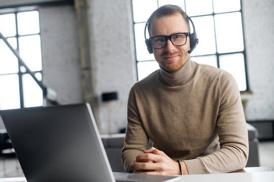 Confident operator with headset and glasses, looking at the camera, sitting at the laptop, worker of the year, enjoys his work, workplace, listening the client attentively, can solve your request