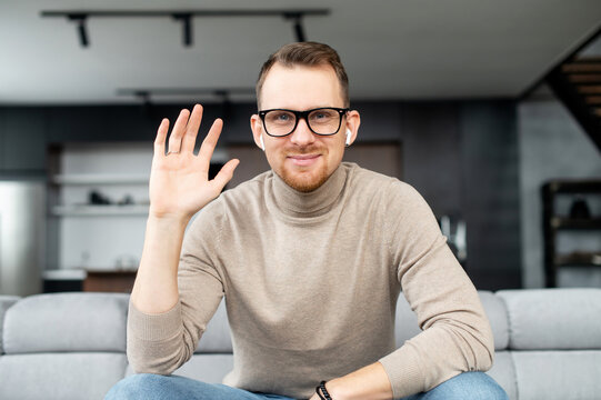 Young adult European man in elegant black glasses, looking at the camera, smiling and waving the hand, say hello, greeting by video, speaking on webcam, positive person, with white earphones, stylish