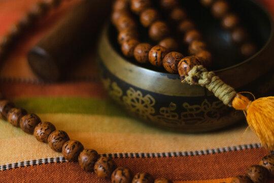 Tibetan bowl with a mala on a nice colorful cushion