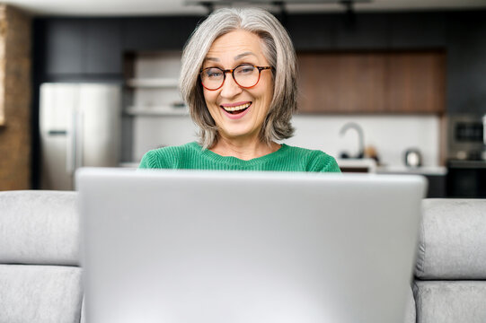Surprise senior woman looking at the laptop screen sitting on the coach at home, an elderly lady wearing eyeglasses saw unexpected good news or received pleasantly message