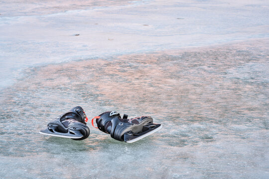 pair of men ice skates on a frozen lake with sunset reflections
