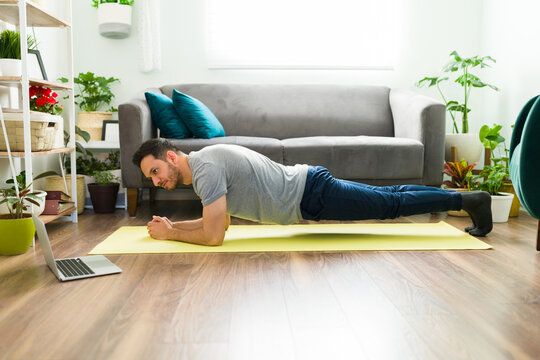 Fit man with a healthy lifestyle exercising with a video tutorial