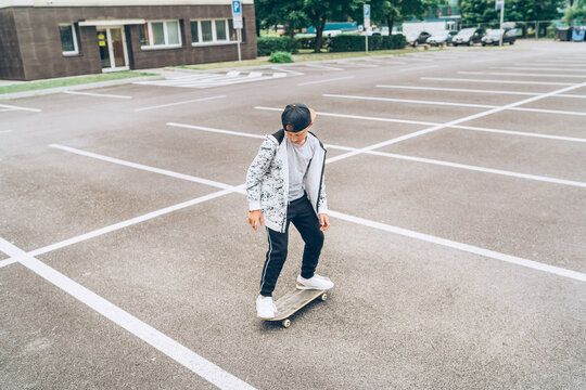 Teenager skateboarder boy riding a skateboard on asphalt playground with white lines doing tricks. Youth generation Freetime spending concept image.