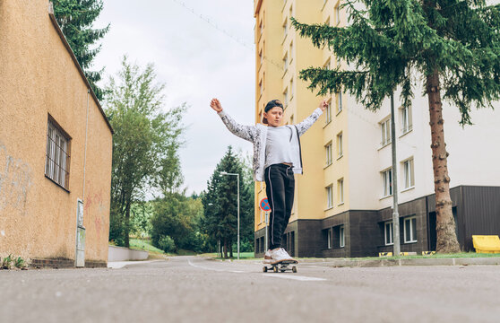 Teenager skateboarder boy in baseball cap riding a skateboard on asphalt street road. Youth generation Freetime spending and an active people concept image.