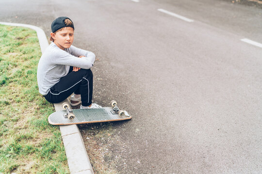 Teenager skateboarder boy with a skateboard sitting on the asphalt road border and resting after he made tricks. Youth generation Freetime spending concept image.