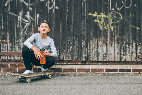 Smiling teenager skateboarder boy sitting beside a wooden grunge graffiti wall with skateboard and Water bottle flask. Youth generation Freetime spending and an active people concept image.