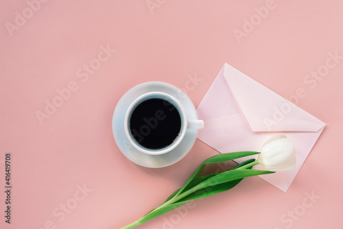 Cup of coffee, envelope and white tulip on coral pink background. Women's day or Mother's day concept. Top view, flat lay.