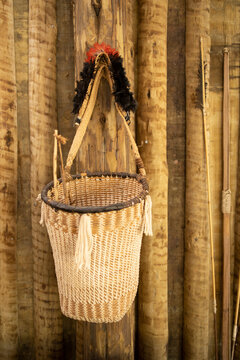 Modern luxury summer holiday or vacation beach house living room interior decoration. Indigenous style handcrafted braided straw basket hanging on rustic wooden wall.