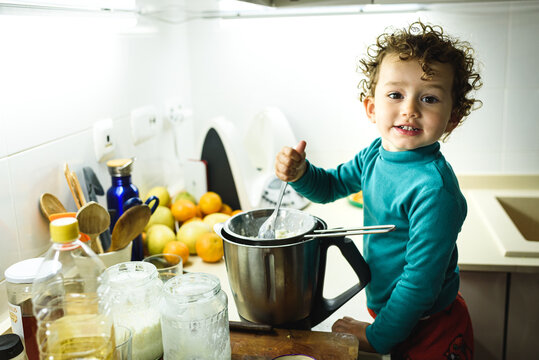 Young baby girl helps prepare a cake using a food processor.