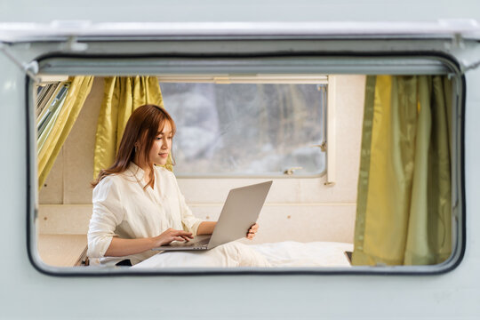 woman using laptop computer on bed of a camper RV van motorhome