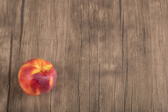 Red and yellow peaches isolated on a wooden deck