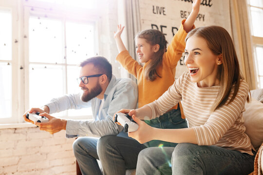 Girl supporting parents playing videogame