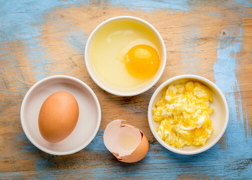 scrambled egg abstract - white bowls with eggs against grunge painted wood