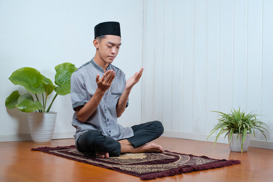 Young Asian muslim man pray on the prayer rug