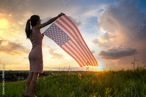 Young woman with USA national flag standing outdoors at sunset. Positive girl celebrating United States independence day. International day of democracy concept.