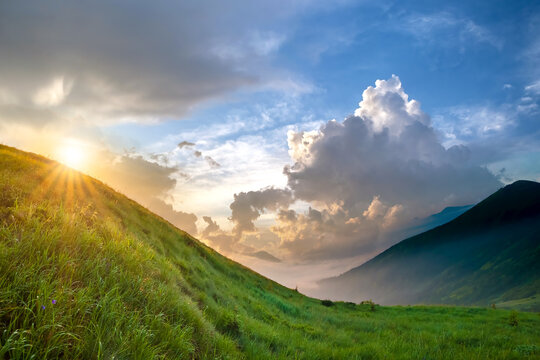 Beautiful view of green grassy hills at the foot of magnificent distant mountain on bright sunny summer evening.