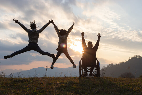 Silhouette Disabled handicapped woman in wheelchair with raised arms and children jumping at sunset. happy family concepts.