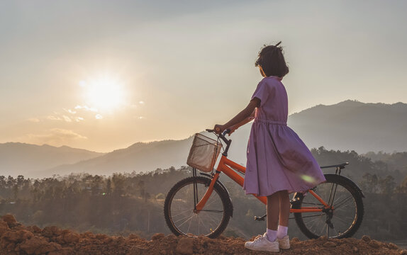 Silhouette little girl with bike looking sunset on mountain