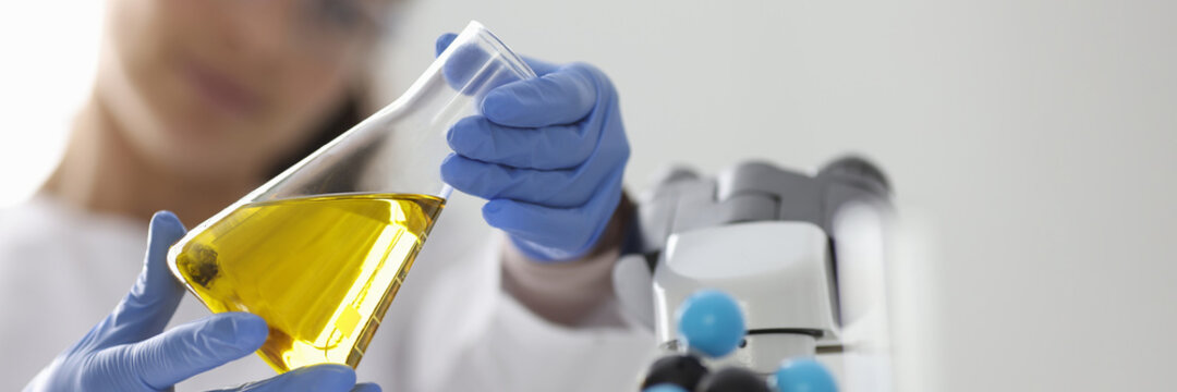 Researcher holds flask with yellow liquid. Research of properties of oil and oil products concept