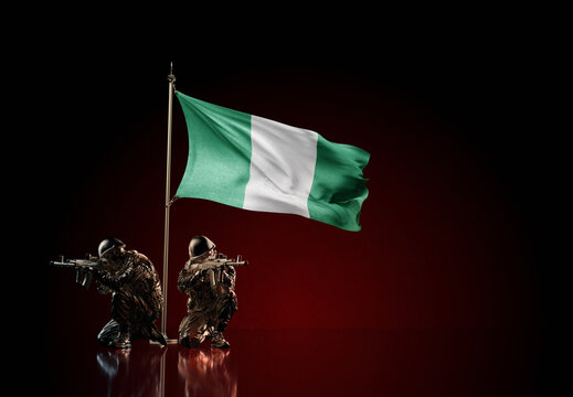 Concept of military conflict. Waving national flag of Nigeria. Two soldier statue guards defending the symbol of country against red wall